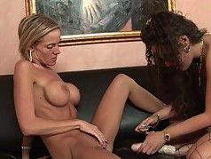 Busty blonde and brunette fuck with a toy in the living room